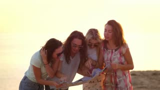 Female friends looking route map. Tourist lost way at summer coast. Cheerful women looking guide map. Traveling lifestyle. Women group searching destination place