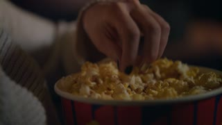 Female hand picking popcorn from paper bucket closeup. Close up of woman eating pop corn at cinema. Movie food concept. Female hand taking popcorn in bucket at cinema