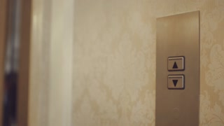 Female hand pushing button for calling elevator in apartment corridor. Close up woman hand pressing lift button down on panel