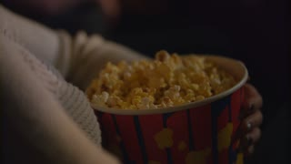 Female hand taking popcorn flakes from paper container. Eating pop corn at cinema in slow motion. Close up of female hand in bucket of popcorn at movie theater