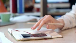 Female hand using mobile phone for calculate profit at office workplace. Financial business company accounting. Close up of woman hand calculate on smart phone and writing in notebook at office