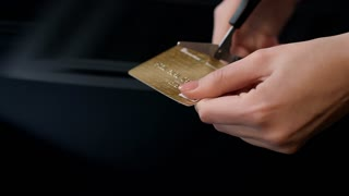 Female hands cutting credit card with scissors. Debit card account closing. Scissors cutting bank card. Stop to pay money. Financial crisis concept. Destroy credit card. Stop spending on shopping