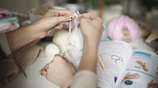 Female hands learning to knit using knitting pattern. Woman learning knitting yarn friend. Woman leisure