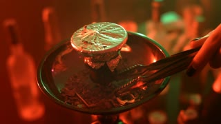 Female hands take hot charcoal with metal tweezers for hookah. Close up hand put hot coal on bowl of nargile. Coal for hookah smoking is placed on bowl with a falcon. Hot coal for shisha smoking