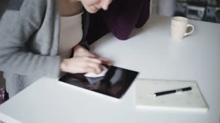 Female hands wiping surface screen tablet pc with cloth. Young woman cleaning screen tablet computer lying on table. Woman care tablet pc