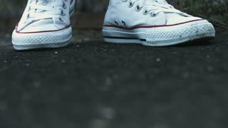 Female legs in fashion white sneakers standing on place on ground. Close up woman legs in white converse on feet walking on ground. Youth lifestyle concept