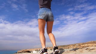 Female legs in shorts jumping on rocky shoreline. Happy woman jumping at rocky cliff near sea. Woman jumping for joy on rocky beach back view. Joyful girl enjoy holiday