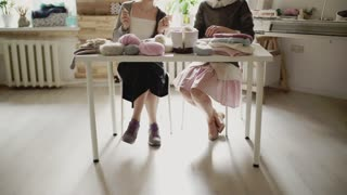 Female legs sitting at table and knitting needles. Two woman knitting yarn in home. Two woman friends together knitting wool clothes in workroom