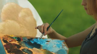 Female painter mixing oil paints on artist palette with paintbrush. Close up girl painter standing near canvas on easel. Creative female artist painting picture outdoors