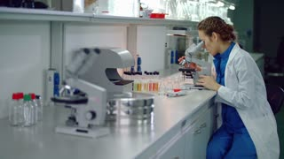 Female researcher using microscope in research lab. Woman scientist looking microscope in laboratory. Lab assistant bring notepad to science woman. Woman researcher doing microscope research in lab