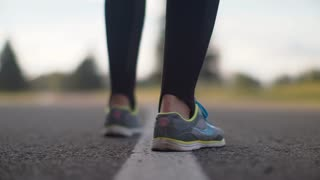 Female runner legs start to run on road. Closeup of woman legs in running shoes start to run on asphalt road. Close up of runners feet in sport shoes on road. Female athlete start run