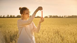 Female scientist doing biological research. Agro scientist holding test tube with pink liquid. Agriculture and science concept