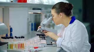 Female scientist with microscope in lab. Woman scientist doing microscope research. Microscope scientist working in lab. Lab scientist looking in microscope. Science laboratory research