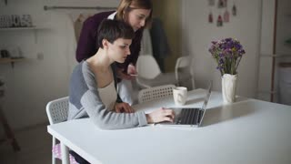 Female students searching internet on laptop computer. Two woman looking news in laptop computer at home room. Young woman working on notebook at table