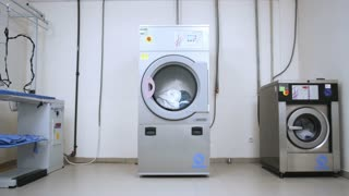 Female worker take away clothes from drying machine at laundry room. Woman removing cloths from washing machine at industrial laundry. Dryer laundry machine in laundry service