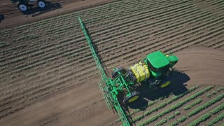 Fertilizer spreader. Agricultural sprayer irrigation on farming field. Spraying machine watering plant on agricultural field. Aerial view process pesticide spraying. Watering plant. Fertilizing plant