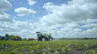 Fertilizer spreader. Spraying machine irrigating farming field. Agricultural sprayer transformed after watering field. Agriculture fertilizer for field irrigation. Farming machinery for watering plant