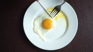 Finish eating fried eggs. Male hand cutting fried egg with knife and fork. Close up of cutting fried eggs. Finishing morning breakfast. Traditional breakfast. Healthy breakfast. Crossed cutlery