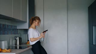 Fit girl in sportswear drinking water in kitchen. Woman runner in white t-shirt and black fitness leggings. Beautiful girl listening music in headphones and drink water