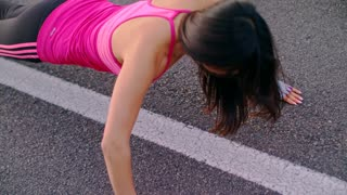 Fitness woman push ups on city road. Closeup of female athlete doing push up exercise. Top view of sport woman pushing on asphalt road. Close up of sporty woman fitness workout outdoor. Woman pushups