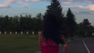 Fitness woman running away on road. Back view of fitness woman jogging in park at morning. Jogging woman at sunrise. Sport girl jogging in slow motion. Woman fitness workout outdoor