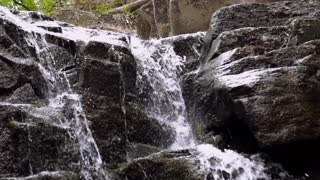 Flowing water in peaceful place. Cascade fall downhill in deep forest. Waterfall flow on stone. Water quickly fall down in rocky path. Beautiful water stream landscape