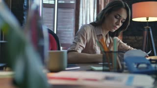 Focused business woman writing finance report in home office. Concentrated financial analyst calling on smartphone in office at evening. Female marketer working with documents at workplace