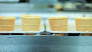 Food production line. Waffle cone manufacturing. Empty waffle cup on conveyor belt. Ice cream factory. Waffle cup manufacturing line. Food industry. Automated production. Ice cream production line