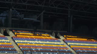 Football stadium with empty tribunes. Empty different colors seats in sports stadium. Section of plastic chairs on grandstand. Modern open olympic arena at daylight