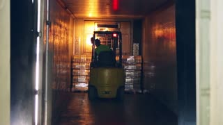 Forklift truck shipping packaged milk bottles. Forklift working in warehouse with milk bottles. Pallet transport in dairy factory. Milk delivery process