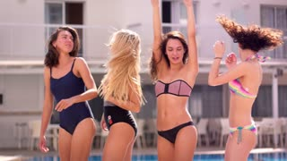 Four girls in swimsuits dancing and having fun. Friendship concept. Summer party near swimming pool. Sexy women dancing in swimwear. Enjoy pool party. Sexy girls have fun at resort