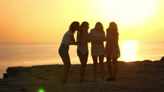 Four tourists with map at beach sunset. Summer woman speaking on sea sunset. Four girls silhouettes talking at evening beach. Female summer travel. Female friends find road on map
