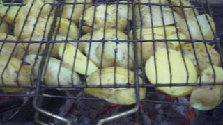 Fresh potatoes cooking on barbeque grill on summer picnic. Close up process preparation barbeque vegetable on hot coals during camping at nature