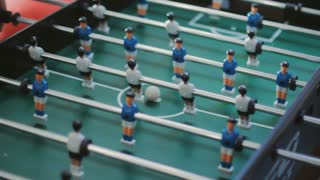 Friends having fun together playing foosball. Colleagues playing table football on break. Office people enjoying table soccer game. Close up of table football kicker game