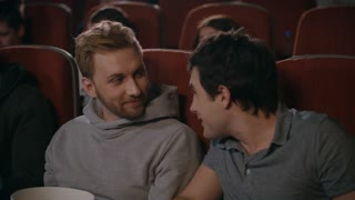 Friends watching movie in cinema. Uncultured man preventing to friends watching film. Guy closing by hand from annoying guy in movie theatre