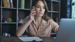 Frustrated woman talking on mobile phone. Business lady working in startup office. Disappointed woman working on business project on laptop. Close up of female specialist speaking phone at workplace