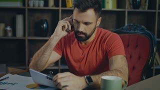 Furious man talking on phone at desk. Angry business man talking on cell phone in home workplace. Unsuccessful conversation of businessman talking on mobile phone in cozy office