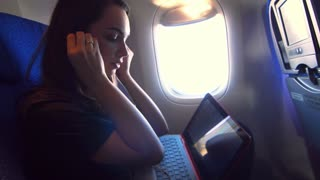 Girl listening music on headphones and working laptop at airplane fly. Woman flying on airplane. Modern girl enjoying flying on airplane. Female tourist working laptop on air travel