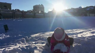 Girl throwing snow in air in slow motion. Happy winter wonderland. Little girl playing with snow back view. Carefree kid enjoy winter holiday