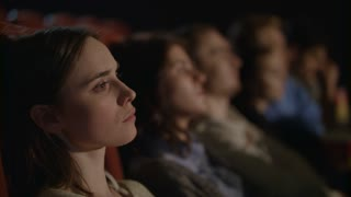 Girl watching movie sitting in cinema chair. Young girl thoughtfully watching film at cinema. Close up of beautiful woman face watching movie at cinema. Sad woman watching drama