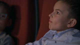 Girl whispering to boy watching movie in cinema. Children exchange impressions about film. Close up of boy watching cinema movie in slow motion. Child movie entertainment