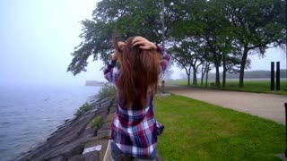 Going girl back view. Back view of woman in casual dress. Walking woman in park sea. Back view of woman going on parapet near sea. Woman going on stone beach in fog weather