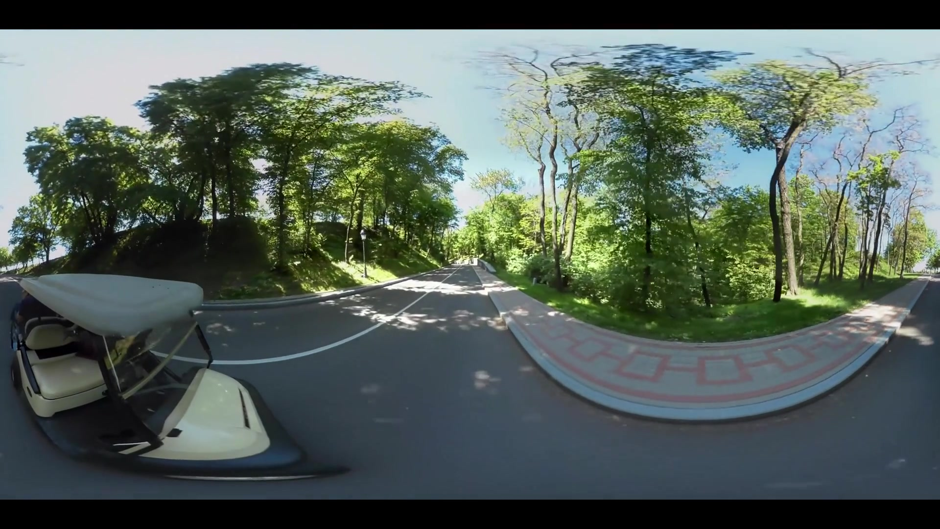 Golf cart moving on road along green field. Panoramic view golf cart driving on road past green golf course 360 degrees. Landscape green golf course 360 video
