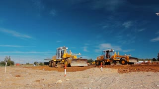 Grader leveling ground on construction site before kick off building project. Modern heavy vehicle in mining industry. Preparing building territory for new construction. Mining machinery