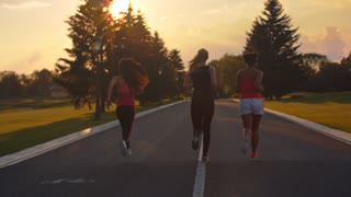 Group of women running at sunset. Back view of three fitness women running in park at sunset. Weight loss training at evening. Sporty women fitness workout outdoor. Sport women running group