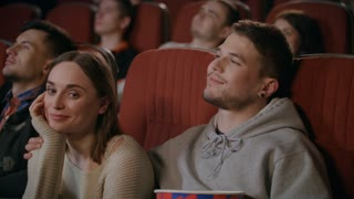 Guy gently embracing girl while watching movie in cinema. Romantic date at movie theatre. Close up of love couple enjoy movie