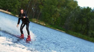 Guy rushing along forest lake on wakeboard touching water surface by hand. Extreme sport wakeboarding. Man wakeboarder riding on river. Extreme lifestyle. Wakeboarding boat rider in waterproof cloth