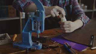 Handmade leather manufacturing. Craftsman making leather purse. Craftsman hands doing leather impregnation in home workshop. Craft man manufacturer processing finished product