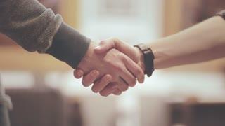 Handshake man. Friendly handshake of two men. Close up of men greeting with handshake. Friends handshaking of two hands. Business partners handshaking
