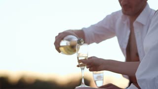 Handsome man pouring champagne in wineglasses at sunset. Happy love couple relaxing outdoor. Romantic date with champagne at sunset